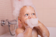 Funny toddler in a foam taking a bath and looking up Royalty Free Stock Photo