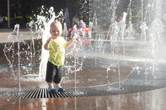 Funny toddler in fountain. Cute baby boy having fun and plaing in fountain. Stock Image