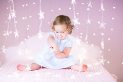 Funny toddler girl between beautiful pink lights Royalty Free Stock Image