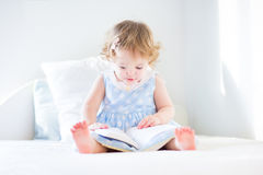 Funny toddler girl in a blue dress reading book Royalty Free Stock Images