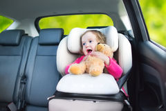 Funny toddler girl in a car seat during vacation trip. Cute curly laughing and talking toddler girl playing with a toy bear enjoying a family vacation car ride Stock Photo