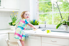 Funny toddler girl in colorful dress washing dishes royalty free stock image