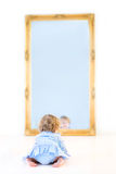 Funny toddler girl with curly hair in front of mirror Stock Photography