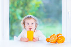 Funny toddler girl drinking orange juice Stock Photos