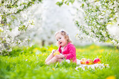 Funny toddler girl eating apple in a blooming garden Royalty Free Stock Photography