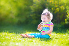 Funny toddler girl eating ice cream in a garden Stock Images