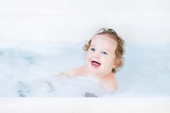Funny toddler girl having a bath with foam Stock Images