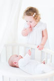 Funny toddler girl hushing her newborn baby brother Royalty Free Stock Images