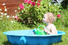 Funny toddler girl playing in bath in the garden Royalty Free Stock Image
