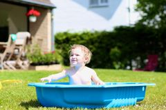 Funny toddler girl playing in bath in the garden Stock Photography