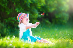 Funny toddler girl playing with butterfly