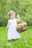 Funny toddler girl playing with a flower basket Stock Photo