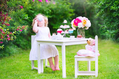 Funny toddler girl playing tea party with a doll. Adorable funny toddler girl with curly hair wearing a colorful dress on her birthday playing tea party with a Royalty Free Stock Photos