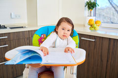 Funny toddler girl reading a book in kitchen Royalty Free Stock Photo