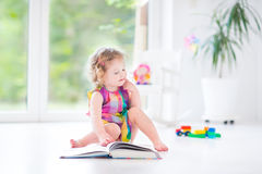 Funny toddler girl reading book in sunny bedroom Royalty Free Stock Photos