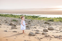 Funny toddler girl running at the beach at sunset stock photos