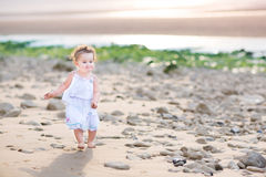 Funny toddler girl running at the beach at sunset Stock Photo