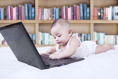 Funny toddler with laptop and bookcase Stock Images
