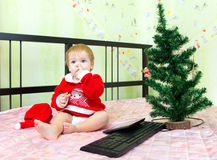 Funny toddler in new year suit picks his nose on the bed. Near Christmas tree Royalty Free Stock Photos