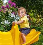 Funny toddler sitting on baby swing. Pretty smiling Royalty Free Stock Photography
