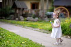 Funny toddler in sunglasses girl with a toy Royalty Free Stock Images