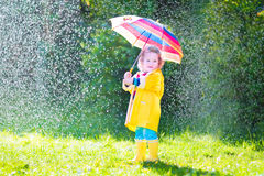 Funny toddler with umbrella playing in the rain. Funny cute curly toddler girl wearing yellow waterproof coat and boots holding colorful umbrella playing in the Royalty Free Stock Image