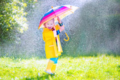 Funny toddler with umbrella playing in the rain. Funny cute curly toddler girl wearing yellow waterproof coat and boots holding colorful umbrella playing in the