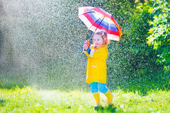 Funny toddler with umbrella playing in the rain. Funny cute curly toddler girl wearing yellow waterproof coat and boots holding colorful umbrella playing in the Stock Photo