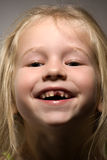 Funny toothless smile. Funny smiling little girl without one front tooth stock photography