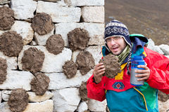 Funny tourist eating yak cow dung. Royalty Free Stock Image