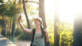 Funny tourist girl in hat taking selfie photos with smartphone camera during travelling and hitchhiking. At countryside stock video