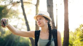 Funny tourist girl in hat taking selfie photos with smartphone camera during travelling and hitchhiking royalty free stock image