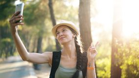 Funny tourist girl in hat taking selfie photos with smartphone camera during travelling and hitchhiking stock image