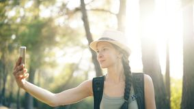 Funny tourist girl in hat taking selfie photos with smartphone camera during travelling and hitchhiking. At countryside stock video footage
