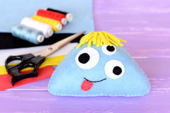 Funny toy monster with three eyes. Blue felt monster, felt sheets, thread set, scissors on lilac wooden background Stock Image