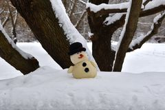 Funny toy snowman standing under a tree stock photo