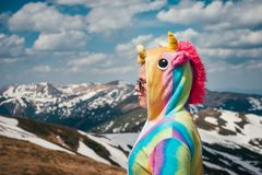 Funny travel concept in the mountain. Closeup portrait shot from back of a female hiker clad in unicorn suit looking at mountain peaks covered with snow on a Stock Image