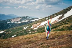 Funny travel concept in the mountain. Full-length portrait shot from back of a female backpacker in a unicorn suit celebrating success on a Carpathian mountains Royalty Free Stock Image