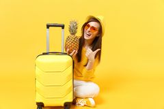 Funny traveler tourist woman in hat showing thumb up, hold fresh ripe pineapple fruit isolated on yellow orange. Background. Passenger traveling abroad on royalty free stock images