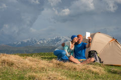 Funny travelers sit next to tent, use table, taking selfie Stock Photo
