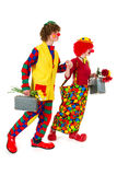 Funny traveling clowns. Funny clowns couple is traveling with suitcases and flowers Royalty Free Stock Images