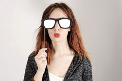 Funny trendy fashion girl with paper glasses playing with emotion Royalty Free Stock Images