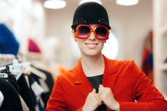 Eccentric Stylish Fashion Girl With Big Sunglasses and Chic Hat. Funny trendy woman wearing a red polka dots blazer and a riding style hat royalty free stock photo