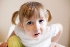 Funny two years old girl with two cute pigtails and quiff royalty free stock image