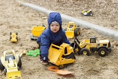 Funny two years toddler playing with a big yellow toy cars on the sand. Spring or autumn photo. royalty free stock image
