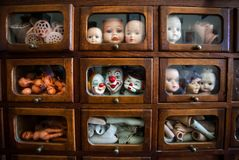 Funny and ugly faces of dolls inside wooden house with small windows. Many parts of heads and legs inside small boxes