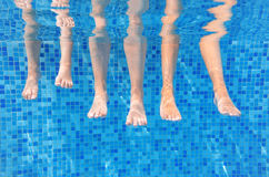 Funny underwater family legs in swimming pool, under water view of mother and kids, vacation and sport Royalty Free Stock Photography