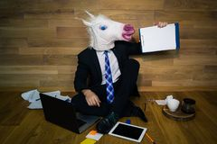 Funny unicorn in a suit and tie smiles and shows a white empty sheet with copy space. Young man in rubber mask sitting on the floor against a wall and works Royalty Free Stock Photography