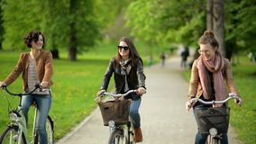 Funny Urban Biking in the Park of Three Cute Female Friends with Amazing Smiles. First Woman has Short Curly Hair, the. Second Wearing Sunglasses and the Third stock video footage