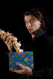 Funny vampire with gift box taking out garlic Stock Photos